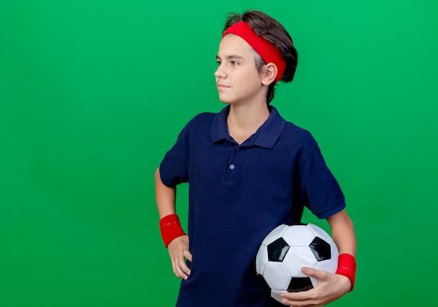 ヘッドバンドとリストバンドを身に着けている自信を持って若いハンサムなスポーティな男の子は、コピースペースのある緑の壁に孤立してまっすぐに見える腰に手を保ちながらサッカーボールを保持している歯列矯正器を持っています