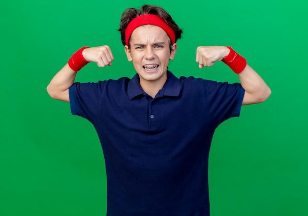 Уверенный молодой красивый спортивный мальчик, носящий повязку на голову и браслеты с зубными скобами, глядя вперед, делая сильный жест, изолированный на зеленой стене