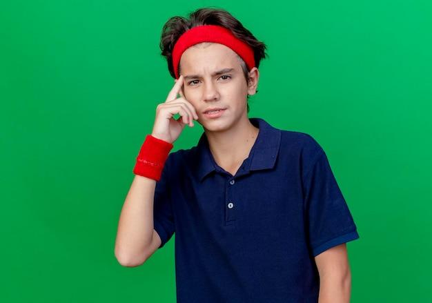 ヘッドバンドとリストバンドを身に着けている自信を持って若いハンサムなスポーティな少年は、コピースペースのある緑の壁に隔離された思考ジェスチャーをしている正面を見て歯科用ブレースを付けています