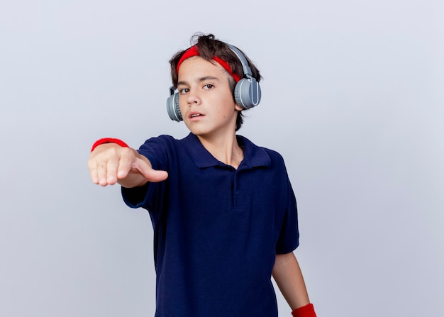 Confident young handsome sporty boy wearing headband and wristbands and headphones with dental braces looking and pointing at camera isolated on white background with copy space
