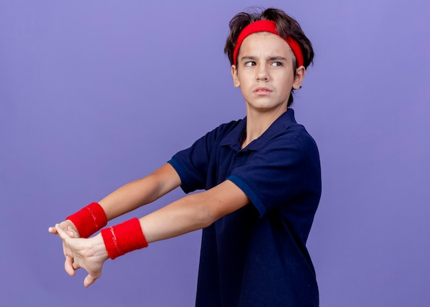 Confident young handsome sporty boy wearing headband and wristbands, stretching hands