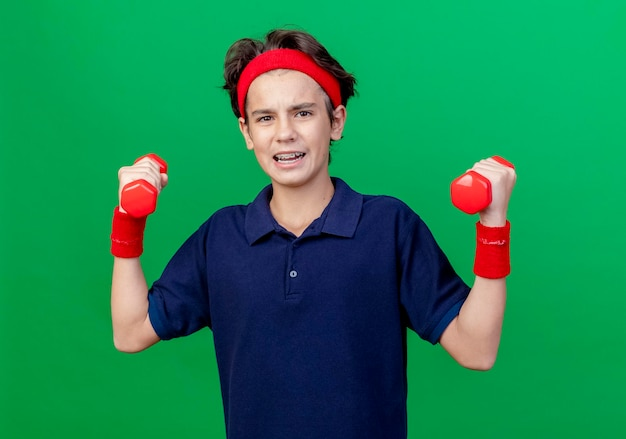 Confident young handsome sporty boy wearing headband and wristbands with dental braces holding dumbbells looking at front isolated on green wall