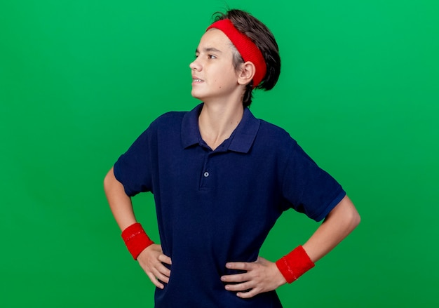 Confident young handsome sporty boy wearing headband and wristbands with dental braces keeping hands on waist looking at side isolated on green wall