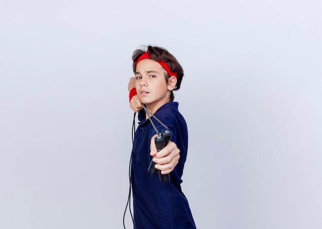 Fiducioso giovane ragazzo sportivo bello che indossa la fascia e braccialetti con bretelle dentali in piedi in vista di profilo tirando la corda per saltare isolato su sfondo bianco con spazio di copia