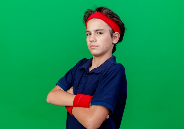 Confident young handsome sporty boy wearing headband and wristbands with dental braces standing with closed posture in profile view looking at camera isolated on green background with copy space