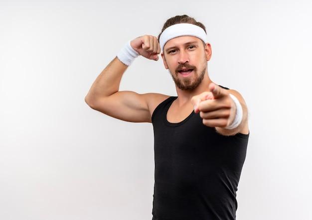 자신감이 젊은 잘 생긴 스포티 한 남자가 머리띠와 팔찌를 착용하고 강한 몸짓과 복사 공간이 흰 벽에 고립 가리키는 가리키는