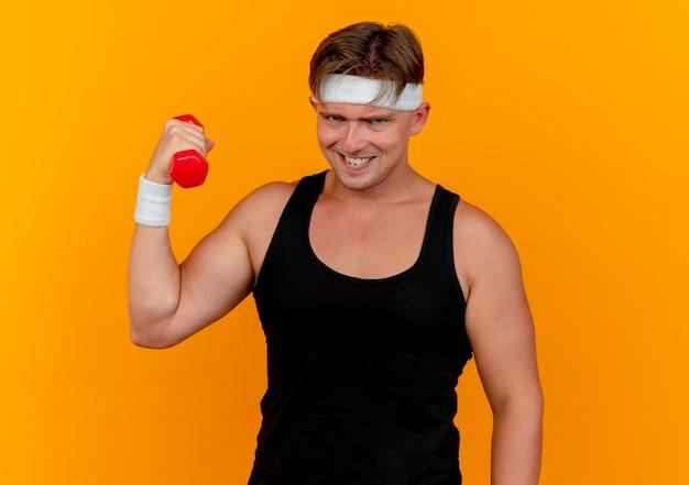 オレンジ色に分離されたダンベルを保持しているヘッドバンドとリストバンドを身に着けている自信を持って若いハンサムなスポーティな男