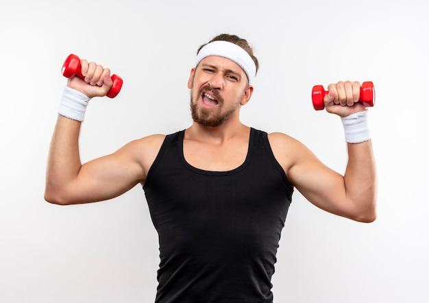 Уверенный молодой красивый спортивный мужчина с повязкой на голову и браслетами, держащими гантели, изолированными на белой стене
