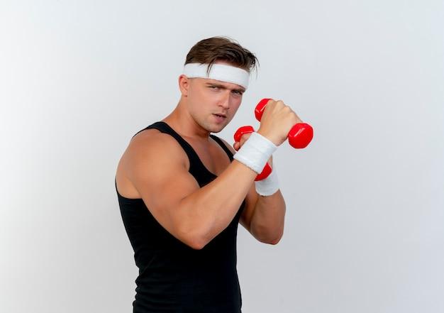 Уверенный молодой красивый спортивный мужчина в головной повязке и браслетах с гантелями, изолированными на белом с копией пространства