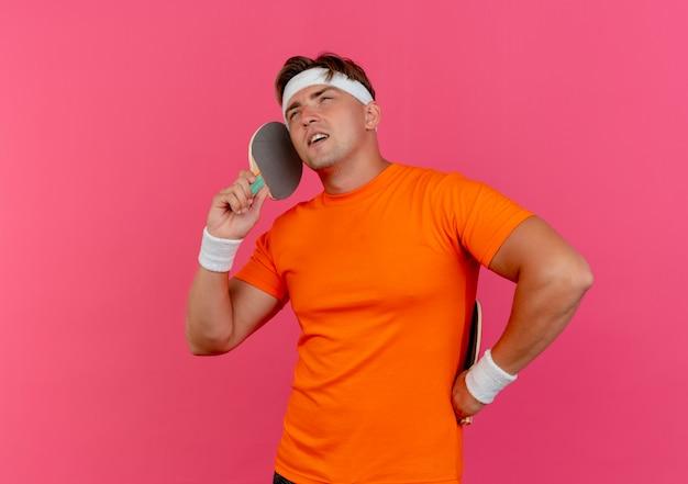 자신감이 젊은 잘 생긴 스포티 한 남자가 머리띠와 팔찌를 착용하고 탁구 라켓을 들고 복사 공간이 분홍색에 고립 된 전화로 이야기하는 척