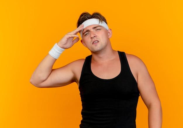 オレンジ色に分離された額に手を置くヘッドバンドとリストバンドを身に着けている自信を持って若いハンサムなスポーティな男