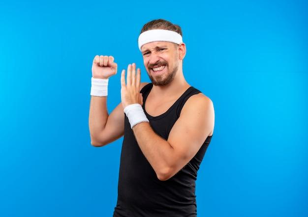 Fiducioso giovane bell'uomo sportivo che indossa fascia e braccialetti stringendo il pugno e puntando con la mano su di esso isolato sulla parete blu con spazio di copia