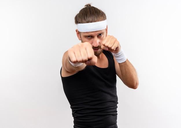 Fiducioso giovane uomo sportivo bello che indossa fascia e braccialetti facendo gesto di boxe isolato su muro bianco