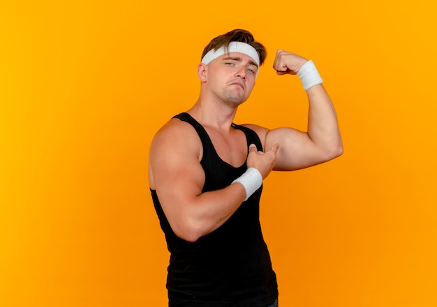 Confident young handsome sporty man wearing headband and wristbands gesturing strong and pointing at his muscles isolated on orange  with copy space