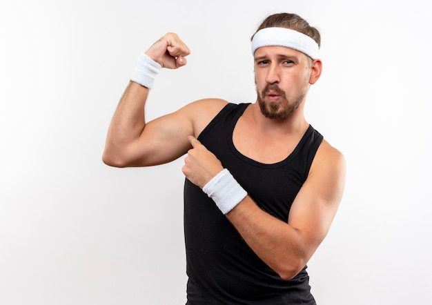 Confident young handsome sporty man wearing headband and wristbands gesturing strong and pointing at his muscles isolated on white wall