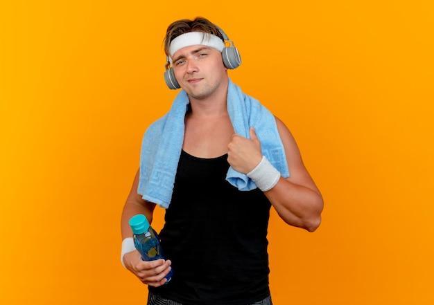 Fiducioso giovane uomo sportivo bello che indossa la fascia e braccialetti e cuffie con asciugamano intorno al collo tenendo la bottiglia di acqua e asciugamano isolato su arancione con spazio di copia