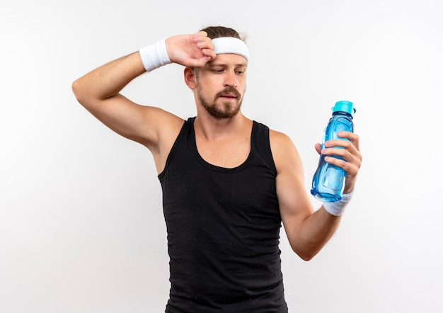 Confident young handsome sporty man wearing headband and wristbands holding and looking at water bottle with hand on head isolated on white wall