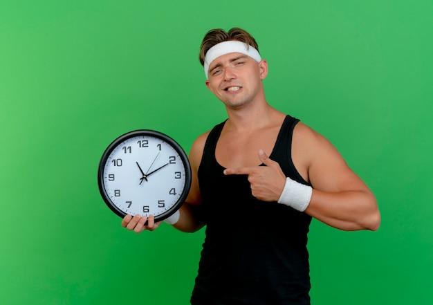Fiducioso giovane uomo sportivo bello che indossa la fascia e braccialetti che tengono e che indica l'orologio isolato sul verde
