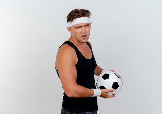 Fiducioso giovane uomo sportivo bello che indossa la fascia e braccialetti in possesso di pallone da calcio isolato su bianco con copia spazio