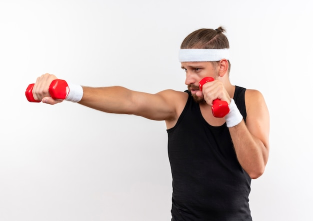 Confident young handsome sporty man wearing headband and wristbands holding and stretching out dumbbells and looking at dumbbell isolated on white wall