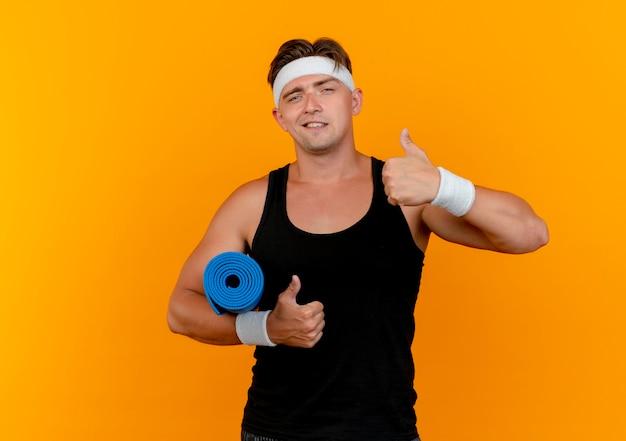 Fiducioso giovane bell'uomo sportivo che indossa la fascia e braccialetti che tengono l'asciugamano e che mostra i pollici in su isolato sull'arancia con lo spazio della copia