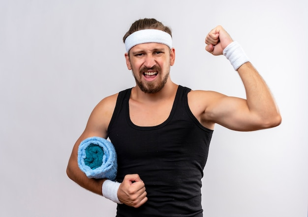 Fiducioso giovane uomo sportivo bello che indossa fascia e braccialetti alzando il pugno e tenendo l'asciugamano isolato sul muro bianco