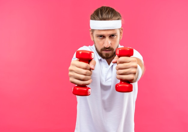 Confident young handsome sporty man wearing headband and wristbands stretching out dumbbells towards  isolated on pink wall with copy space