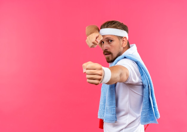 Confident young handsome sporty man wearing headband and wristbands stretching out fists  with jump rope and towel on shoulders isolated on pink wall with copy space