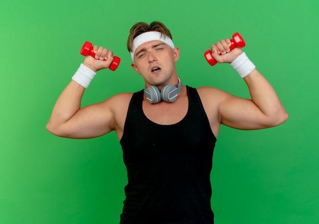 Fiducioso giovane uomo sportivo bello che indossa la fascia e braccialetti con le cuffie sul collo che alza i dumbbells isolati sul verde