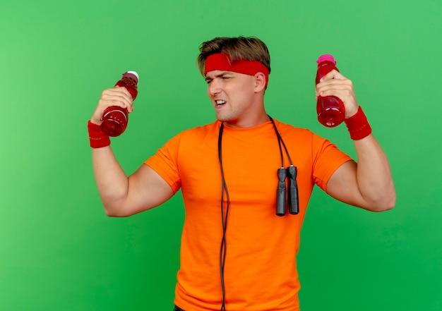 Fiducioso giovane bello sportivo da uomo che indossa la fascia e braccialetti con la corda per saltare intorno al collo tenendo le bottiglie di acqua guardando la bottiglia isolata su verde