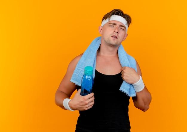Fiducioso giovane uomo sportivo bello che indossa la fascia e braccialetti con asciugamano intorno al collo tenendo la bottiglia di acqua e asciugamano isolato su arancione con spazio di copia