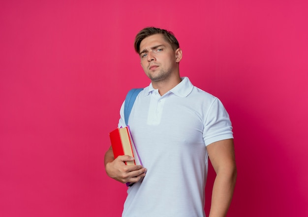 ピンクで隔離の本を保持しているバックバッグを身に着けている自信を持って若いハンサムな学生の男