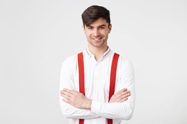 Fiducioso giovane hipster con capelli scuri non rasati in piedi con le braccia incrociate, indossa una camicia bianca, bretelle rosse, sorridente