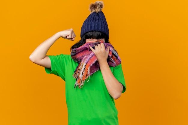 복사 공간 오렌지 벽에 고립 된 강한 제스처를 하 고 스카프로 입을 덮고 겨울 모자와 스카프를 착용 확신 젊은 아픈 백인 여자