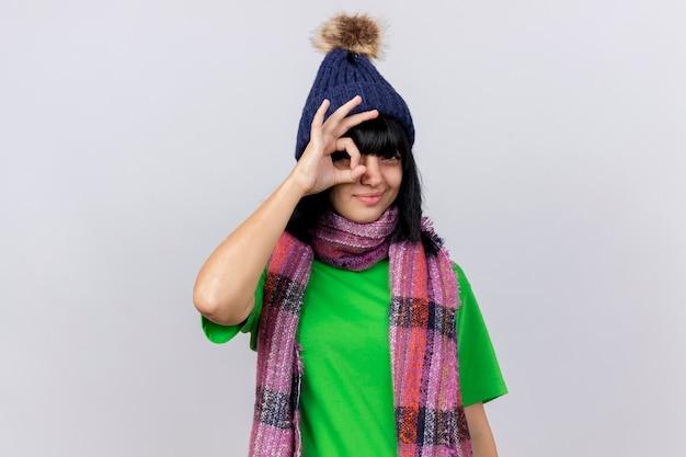 冬の帽子とスカーフを身に着けている自信を持って若い病気の白人の女の子がコピースペースで白い壁に分離された外観のジェスチャーをしている