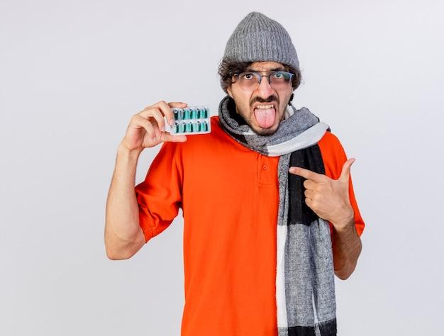 Fiducioso giovane uomo malato con gli occhiali inverno cappello e sciarpa che tiene e che indica al pacchetto di capsule mediche che mostra la lingua guardando davanti isolato sul muro bianco