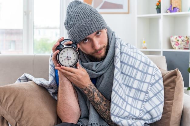 Fiducioso giovane uomo malato che indossa sciarpa e cappello invernale seduto sul divano in soggiorno avvolto in una coperta con sveglia guardando la fotocamera
