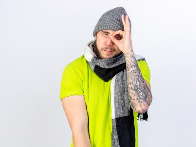 Fiducioso giovane uomo malato che indossa sciarpa e cappello invernale guarda davanti attraverso le dita isolate sul muro bianco