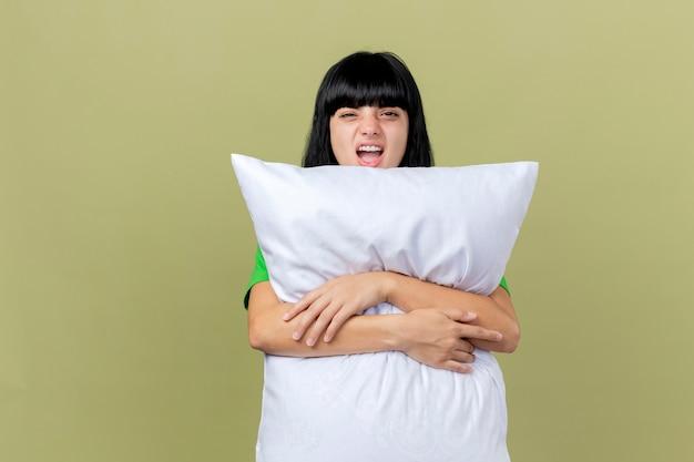 Уверенная молодая больная женщина обнимает подушку, глядя вперед, изолированную на оливково-зеленой стене