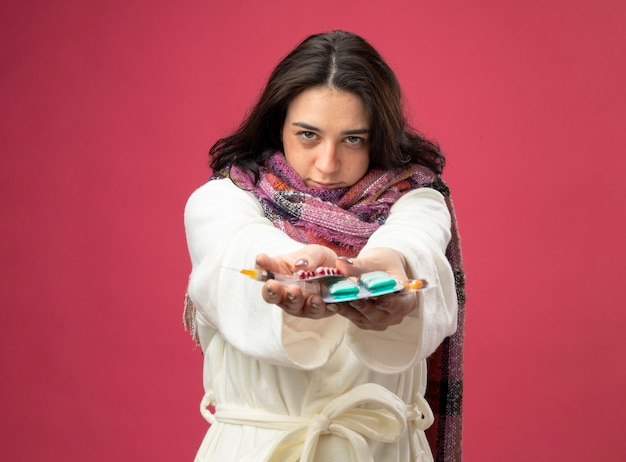 ピンクの壁に隔離された正面を見て、注射器と医療カプセルのパックを正面に伸ばしてローブとスカーフを身に着けている自信を持って若い病気の女性