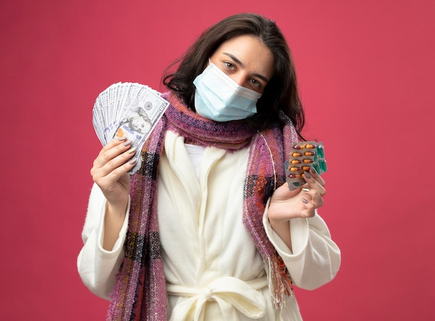 ピンクの壁に隔離された正面を見てお金と医療カプセルのパックを保持しているマスクとローブとスカーフを身に着けている自信を持って若い病気の女性