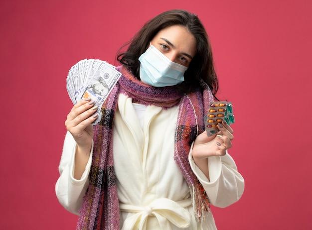 Fiduciosa giovane donna malata che indossa accappatoio e sciarpa con maschera che tiene soldi e confezioni di capsule mediche guardando davanti isolato sul muro rosa