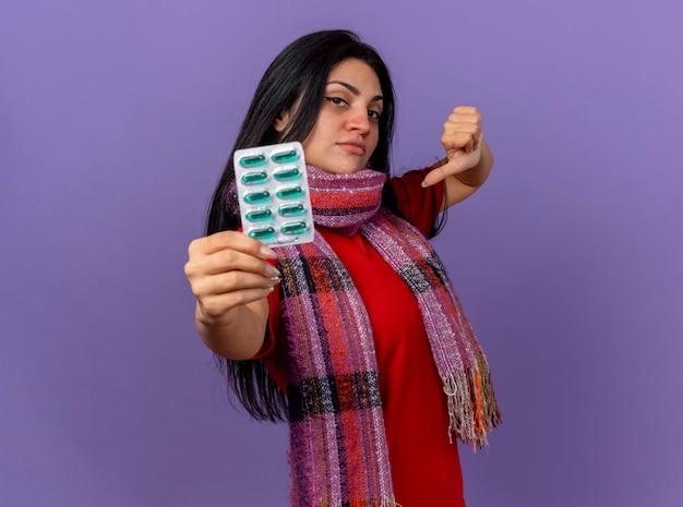 Fiduciosa giovane donna malata che indossa una sciarpa che allunga il pacchetto di capsule verso la parte anteriore guardando davanti che mostra il pollice verso il basso isolato sulla parete viola
