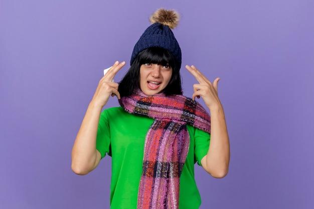 冬の帽子とスカーフを身に着けている自信を持って若い病気の女性が紫色の壁に分離されたピストルジェスチャーをしている錠剤のパックを保持している側を見て
