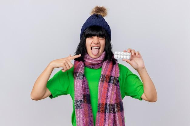 冬の帽子とスカーフを身に着けている自信を持って若い病気の女性は、白い壁に分離された舌を示す正面を見てそれを指している錠剤のパックを示しています