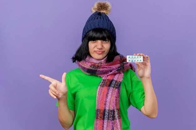 Confident young ill woman wearing winter hat and scarf looking at front holding pack of capsules pointing at side isolated on purple wall with copy space