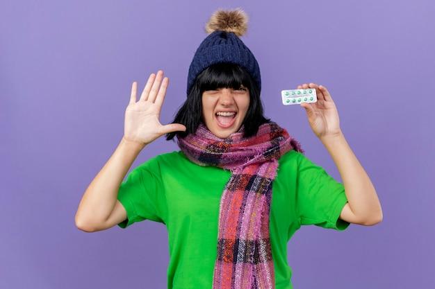 Fiduciosa giovane donna malata che indossa un cappello invernale e sciarpa guardando la confezione anteriore della holding di capsule che mostra la mano vuota isolata sulla parete viola