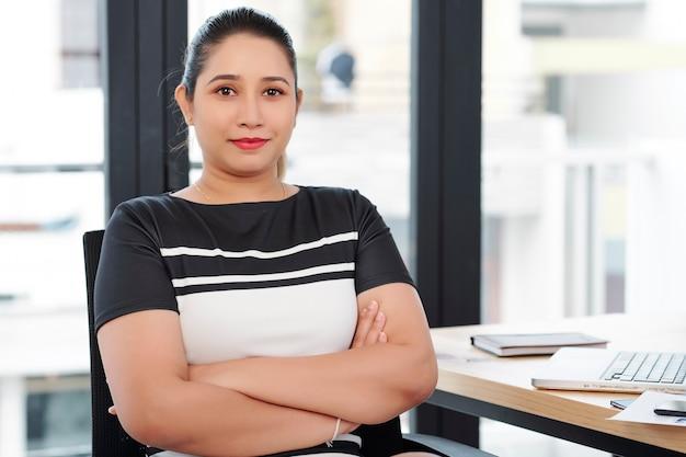 자신감이 젊은 인도 사업가 팔을 접고 사무실에서 그녀의 책상에 앉아있을 때 찾고