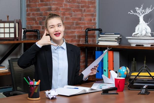 テーブルに座って書類を持っている自信のある若い女性がオフィスでジェスチャーを呼んで