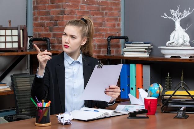 Уверенная молодая дама сидит за столом и читает свои заметки в блокноте, указывая вверх в офисе